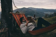 Leave all your worries behind. Handsome young man lying in hammock and reading a book while camping with his girlfriend Royalty Free Stock Photo