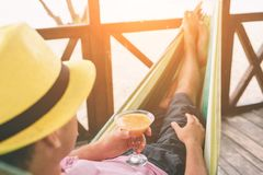 Handsome young man lying in a hammock at a sunny beach by an ocean royalty free stock photo