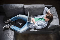 Handsome young man lying on sofa and using laptop, small business people concept. Elevated view of handsome young man lying on sofa and using laptop, small Stock Photos
