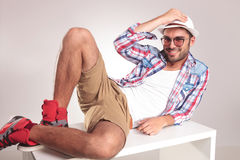 Handsome young man lying on a white table Royalty Free Stock Photos