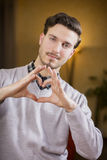 Handsome young man making heart sign with hands Royalty Free Stock Images