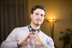 Handsome young man making heart sign with hands stock photography