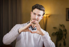 Handsome young man making heart sign with his hands. And fingers. Indoors shot inside a house Stock Photo