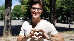 Young man making heart sign with his hands. Handsome young man making heart sign with his hands and fingers. Outdoor in the street Stock Photo