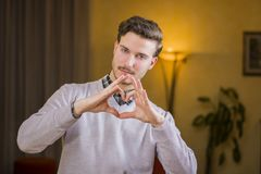 Handsome young man making heart sign with his hands. And fingers. Indoors shot inside a house Royalty Free Stock Image