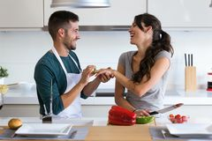 Handsome young man making the joke of asking his girlfriend to marry with a bell pepper in the kitchen at home. royalty free stock photos