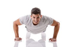 Handsome young man making pushups Stock Photos