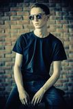 Handsome young man. Male beauty, fashion. Handsome young man posing in sunglasses and black T-shirt by the brick wall. Hair styling royalty free stock photos
