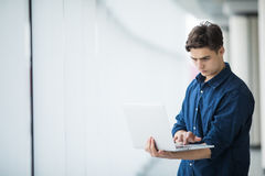 Handsome young man man holding a laptop in hall Royalty Free Stock Photo