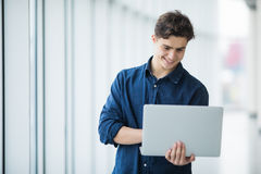 Handsome young man man holding a laptop in hall Royalty Free Stock Images