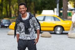 Handsome young man mixed race outdoors portrait, looking in the camera,  on a blurred street background. stock image