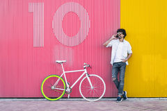 Handsome young man with mobile phone and fixed gear bicycle. Royalty Free Stock Image