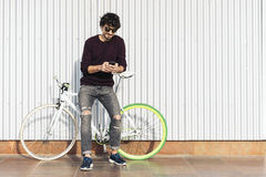 Handsome young man with mobile phone and fixed gear bicycle. Royalty Free Stock Photos