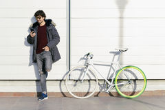 Handsome young man with mobile phone and fixed gear bicycle. Outdoor portrait of handsome young man with mobile phone and fixed gear bicycle in the street Royalty Free Stock Photo