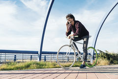 Handsome young man with mobile phone and fixed gear bicycle. Outdoor portrait of handsome young man with mobile phone and fixed gear bicycle in the street Royalty Free Stock Image