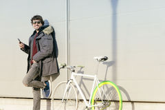 Handsome young man with mobile phone and fixed gear bicycle. Outdoor portrait of handsome young man with mobile phone and fixed gear bicycle in the street Stock Photos