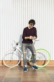 Handsome young man with mobile phone and fixed gear bicycle. Stock Photography