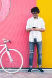 Handsome young man with mobile phone and fixed gear bicycle. Outdoor portrait of handsome young man with mobile phone and fixed gear bicycle in the street Royalty Free Stock Images