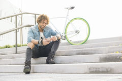 Handsome young man with mobile phone and fixed gear bicycle. Handsome young man with mobile phone and fixed gear bicycle in the street Stock Photography