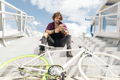Handsome young man with mobile phone and fixed gear bicycle. Handsome young man with mobile phone and fixed gear bicycle in the street Stock Images