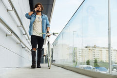Handsome young man with mobile phone and fixed gear bicycle. Handsome young man with mobile phone and fixed gear bicycle in the street Royalty Free Stock Image
