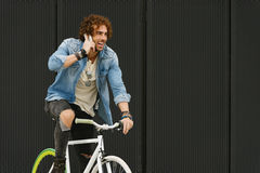 Handsome young man with mobile phone and fixed gear bicycle. Stock Photos