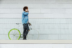 Handsome young man with mobile phone and fixed gear bicycle. Handsome young man with mobile phone and fixed gear bicycle in the street Stock Photos