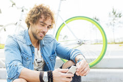 Handsome young man with mobile phone and fixed gear bicycle. Handsome young man with mobile phone and fixed gear bicycle in the street Royalty Free Stock Photos