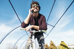 Handsome young man with mobile phone and fixed gear bicycle. Royalty Free Stock Photography