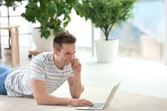 Handsome young man with mobile phone. And laptop on cozy carpet at home Royalty Free Stock Image