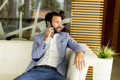Handsome young man with mobile phone. In the office Stock Photography