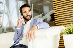 Handsome young man with mobile phone. In the office Royalty Free Stock Photography