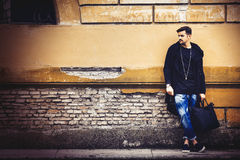 Handsome young man model on street grunge wall. Handsome young man model on the go. On the street leaning against the wall. A beautiful model with a black bag is Royalty Free Stock Photos