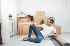 Handsome young man moving to a new home stock photography