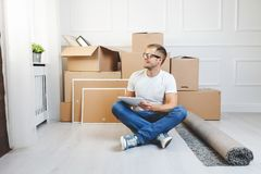 Handsome young man moving to a new home stock photo