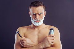 Handsome young man. Handsome naked man with shaving foam on his face is holding a bottle of shaving foam and a razor, on a dark background Stock Photography