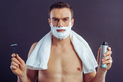 Handsome young man. Handsome naked man with shaving foam on his face is holding a bottle of shaving foam and a razor, on a dark background Royalty Free Stock Photography