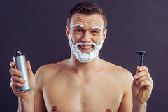 Handsome young man. Handsome naked man with shaving foam on his face is smiling, holding a bottle of shaving foam and a razor, on a dark background Royalty Free Stock Photography