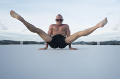 Handsome young man with naked torso doing brake dancing movements on a rooftop. Handsome young man with naked torso and sunglasses doing brake dancing movements Stock Photography