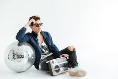 Handsome young man near disco ball and boombox. Picture of handsome young man wearing sunglasses sitting  over white background near disco ball and boombox Stock Image
