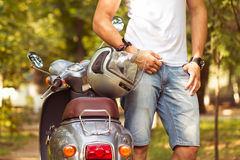 Handsome young man near scooter with a helmet in his hand Stock Images