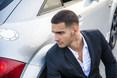 Handsome young man next to car in white shirt Stock Image