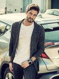 Handsome young man next to car in white shirt. Portrait of young attractive man in white shirt leaning on his new stylish polished car outdoor in city street Stock Images