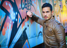Handsome young man next to graffiti covered wall Royalty Free Stock Image