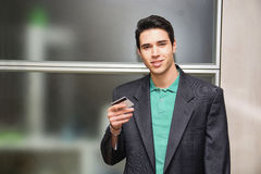 Handsome young man in office holding a credit card Stock Photography