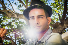 Handsome young man with olive tree's branches behind Royalty Free Stock Images