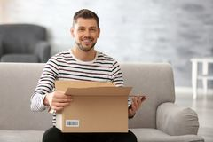 Handsome young man opening box with parcel. While sitting on sofa at home Royalty Free Stock Images
