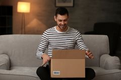 Handsome young man opening box with parcel. While sitting on sofa at home stock image