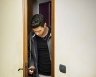 Handsome young man opening door to enter Royalty Free Stock Photography
