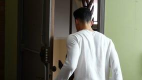 Handsome young man opening door to exit home stock video